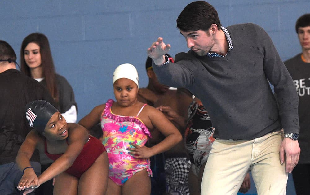 Olympic swimmer Michael Phelps, right, instructs Shakayla Blair, left, during swim team practice at the Haslam Family Club University, in Knoxville, Tenn.