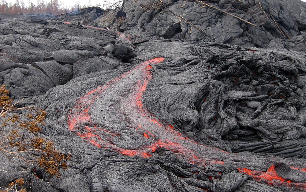 This photo released by the US Geological Survey shows one of many small breakouts of lava on the surface of the June 27 flow immediately upslope of the leading edge near the town of Pahoa on the Big Island of Hawaii.
