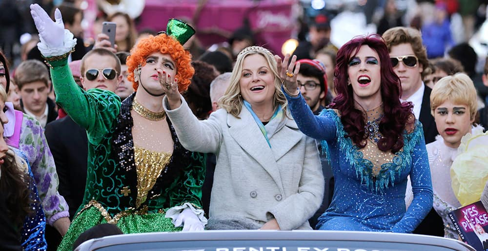 Actress Amy Poehler, waves as she is seated with Jason Hellerstein and Sam Clark, who are dressed in drag, while riding in a convertible through Harvard Square in Cambridge, Mass.