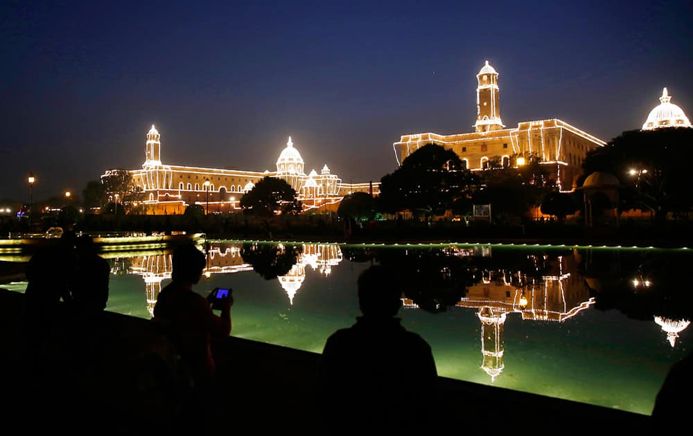 People take photographs and selfies against the illuminated Raisina Hill, which houses India's most important ministries and the presidential palace after Beating Retreat ceremony, in New Delhi.