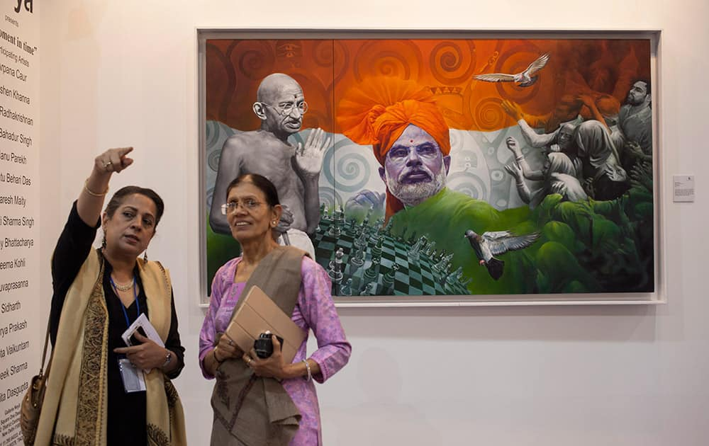 A visitor gestures as she talks to another near a painting titled 'Sons of the same soil' by Viveek Sharma, at the India Art Fair in New Delhi.