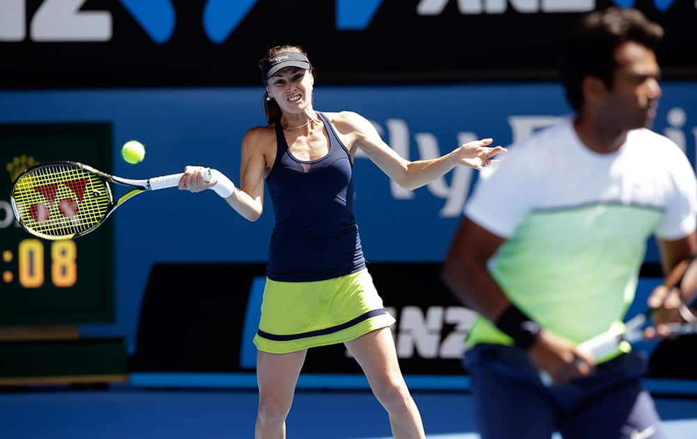 Martina Hingis of Switzerland, left, along with Leander Paes of India, makes a forehand return to Hsieh Su-Wei of Taiwan and Pablo Cuevas of Uruguay during their mixed doubles semifinal match at the Australian Open tennis championship in Melbourne.