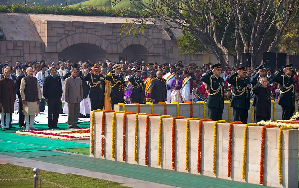 Prime Minister Narendra Modi, stands with other dignitaries as President Pranab Mukherjee, pays his respect at Rajghat, a memorial to Mahatma Gandhi, on his death anniversary in New Delhi.