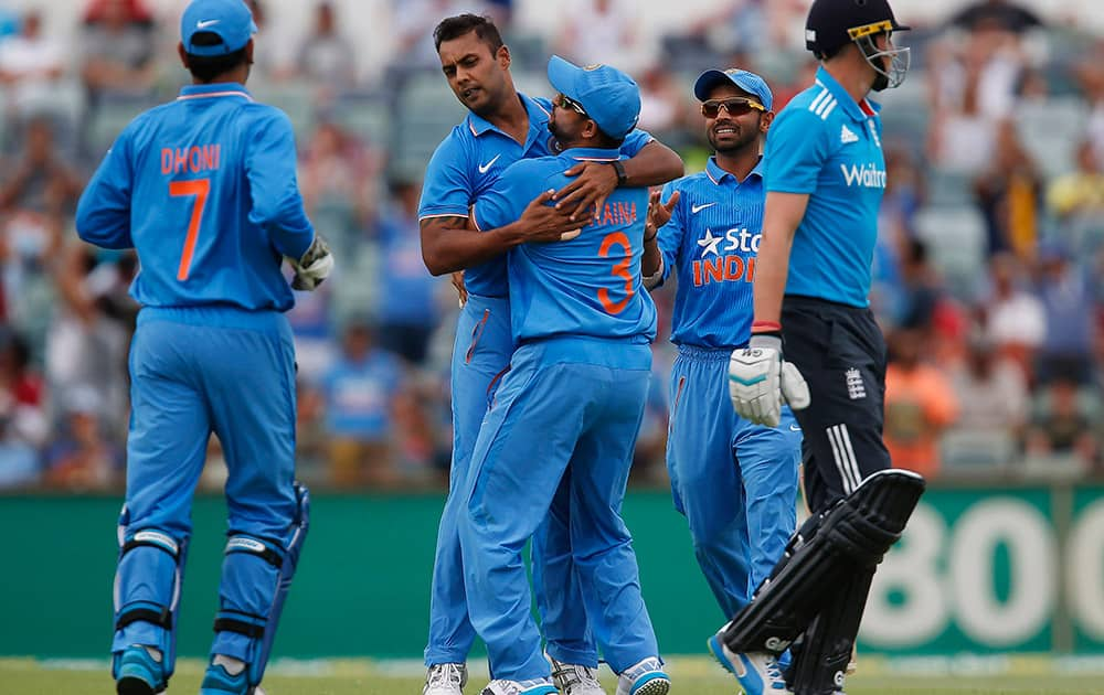 Stuart Binny is congratulated by teammates after taking the wicket of England's Joe Root, during their one day international cricket match in Perth, Australia.