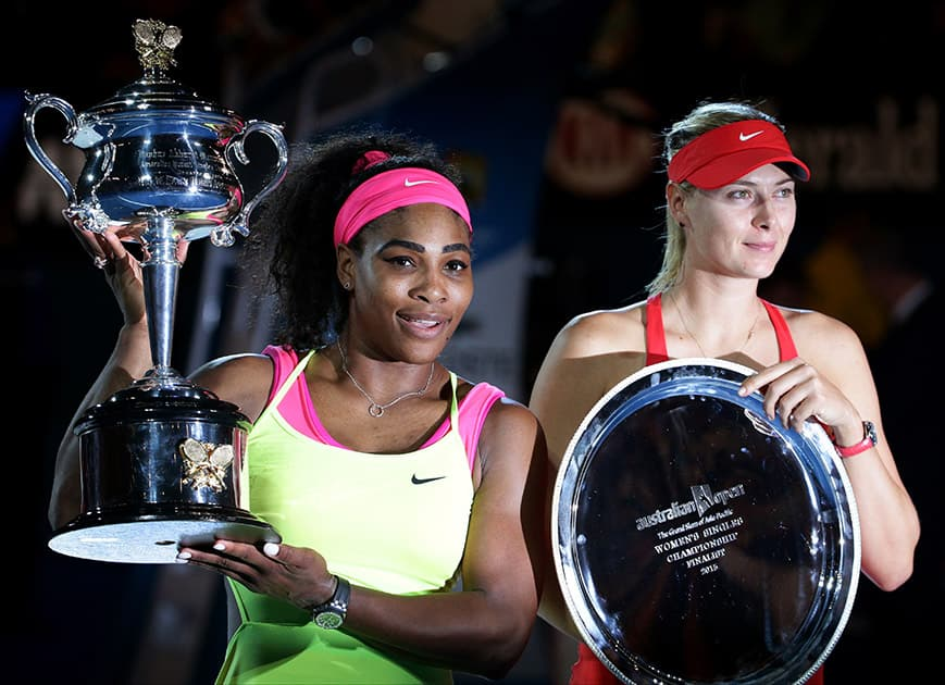 Serena Williams of the US, holds the trophy with runner-up Maria Sharapova of Russia after winning the women's singles final at the Australian Open tennis championship in Melbourne, Australia.