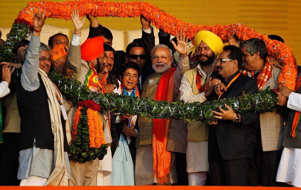 Prime Minister Narendra Modi, center right, waves to the crowd, with the Bharatiya Janata Party's chief ministerial candidate Kiran Bedi, center, standing beside him during an election campaign rally in New Delhi.