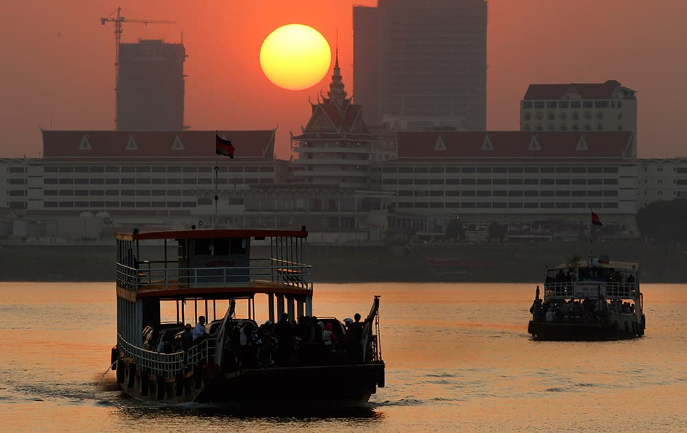 Ferries transport villagers, students and civil servants from Phnom Penh to Arey Ksat across the Mekong River as the sun sets in Phnom Penh, Cambodia.