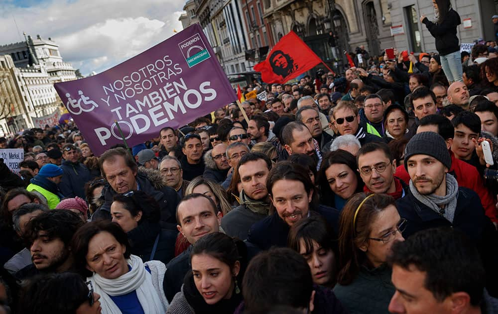 Pablo Iglesias, center right, leader of Spanish Podemos (We Can) left-wing party, smiles as he marches to give a speech at the main square of Madrid during a Podemos (We Can) party march in Madrid, Spain.