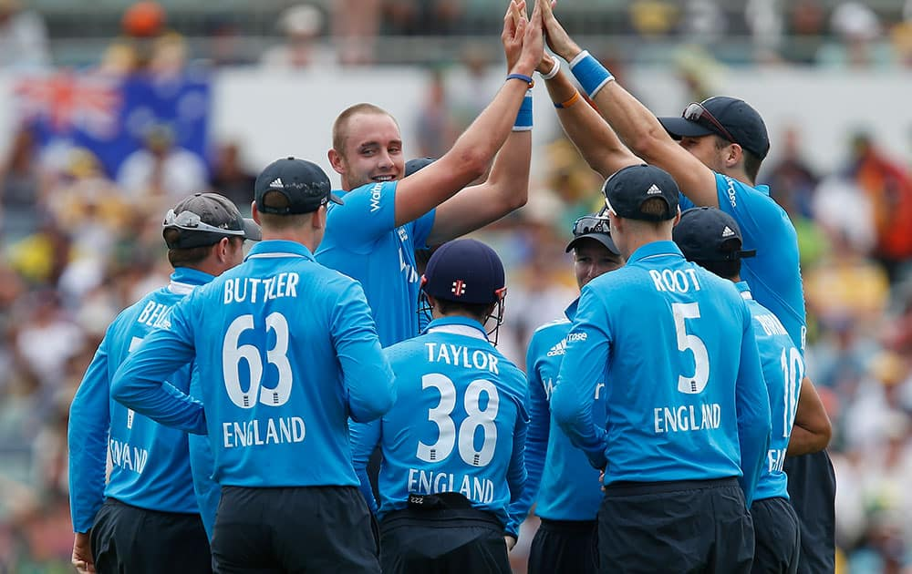 England's Stuart Broad, center, is congratulated by team mates after taking the wicket of Australia's George Bailey during their one-day international cricket match in Perth, Australia.