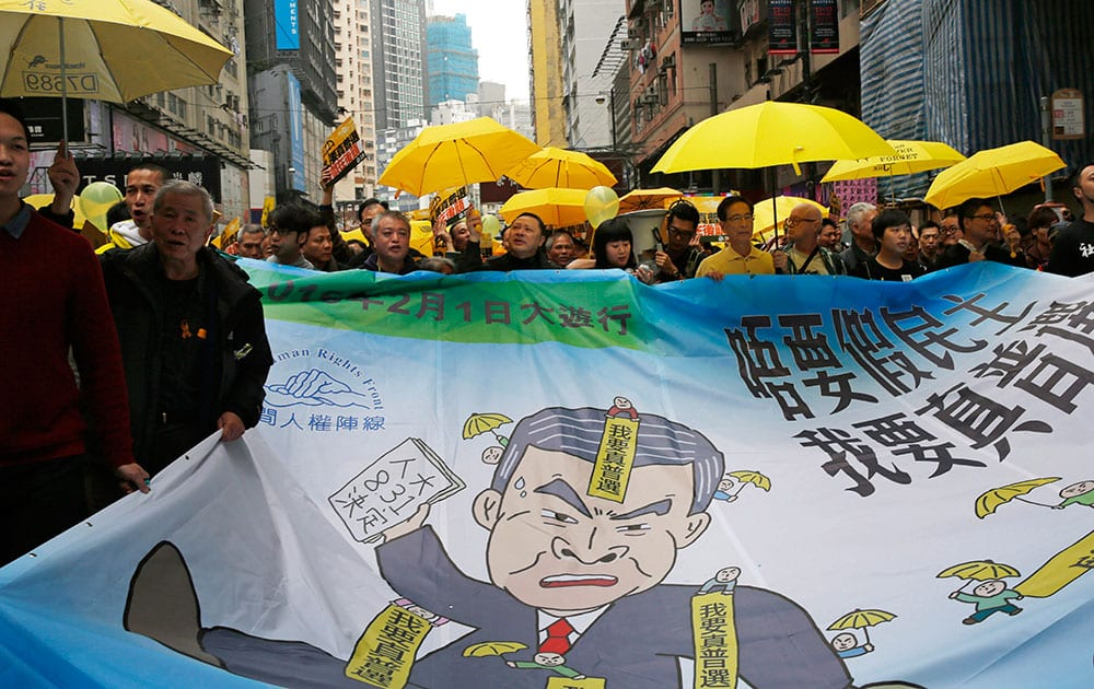 Pro-democracy activists carry a banner depicting Hong Kong Chief Executive Leung Chun-ying during a march to Central, demanding for universal suffrage in Hong Kong.