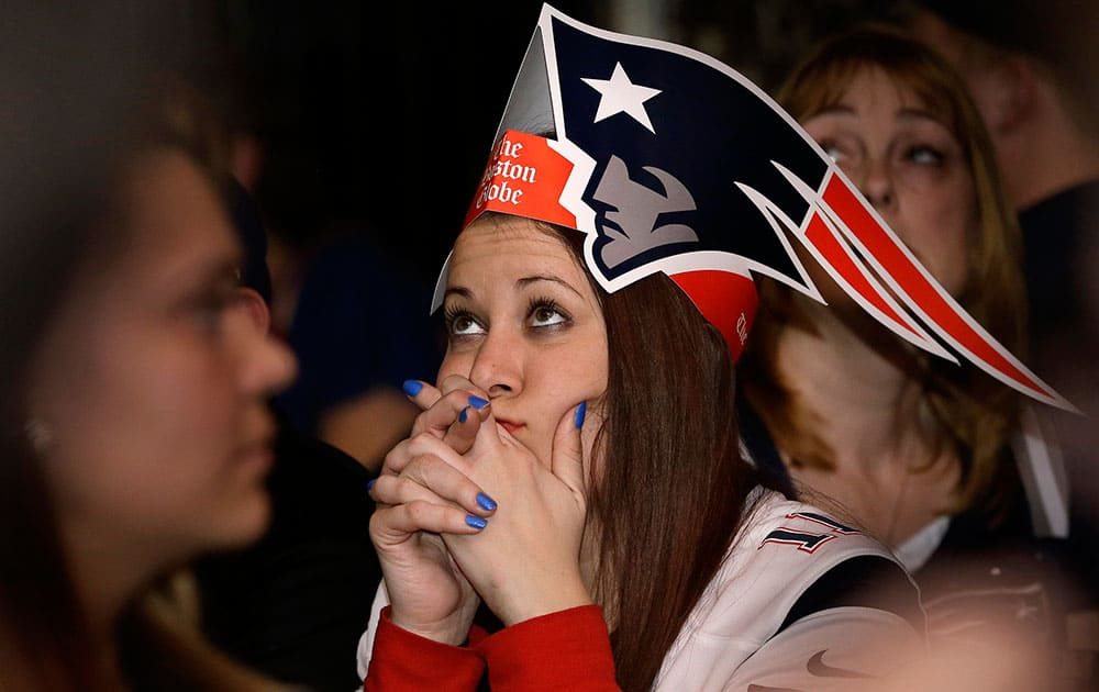 Courtney Lurate, of Boston, watches the New England Patriots play against the Seattle Seahawks in the NFL Super Bowl XLIX football game in Glendale, Ariz., at a bar in Boston.