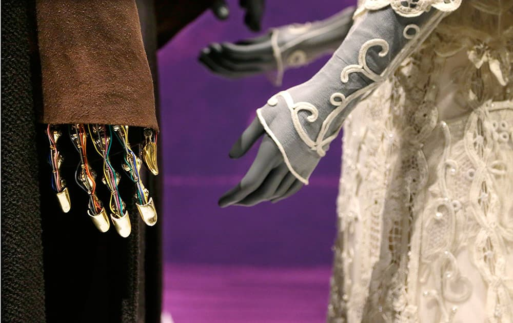 The robotic hand of Anakin Skywalker is seen with his Jedi robe and the wedding gown of his bride, Padme Amidala, while displayed as part of an exhibit on the costumes of Star Wars at Seattle's EMP Museum.