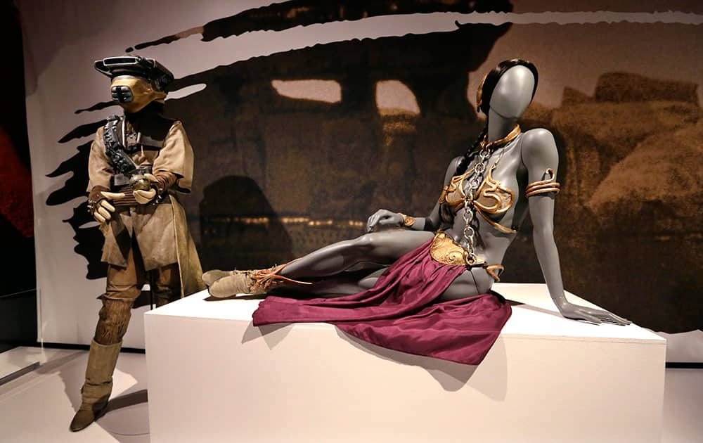 Princess Leia's slave bikini, right, and her Boushh disguise are displayed as part of an exhibit on the costumes of Star Wars at Seattle's EMP Museum.