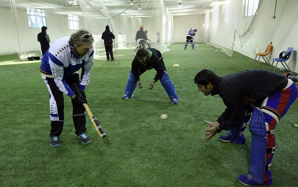 Peter Anderson, coach of Afghan National Cricket team, practices with players at the Kabul cricket academy training center, in Kabul, Afghanistan.