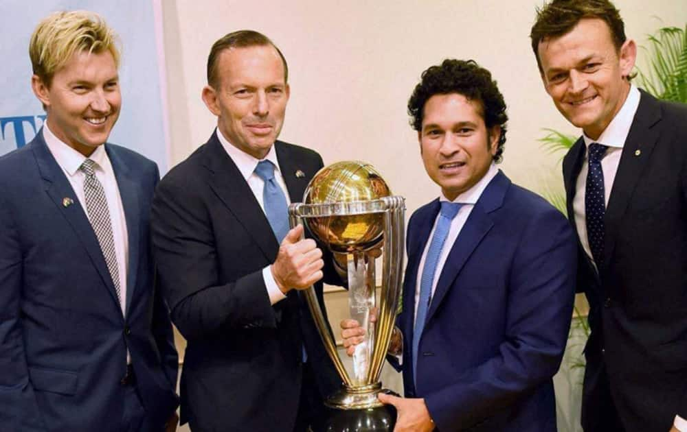 Australian Prime Minister Tony Abbott and legendary cricketer Sachin Tendulkar flanked by former Australian cricketers Adam Gilchrist and Brett Lee pose with the Cricket World Cup trophy during a sporting event.