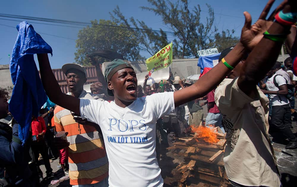 Demonstrators use wood, gas, fire and salt to call forth a spirit to ask for protection during a voodoo ceremony before the start of a protest demanding the resignation of President Michel Martelly in Port-au-Prince, Haiti.