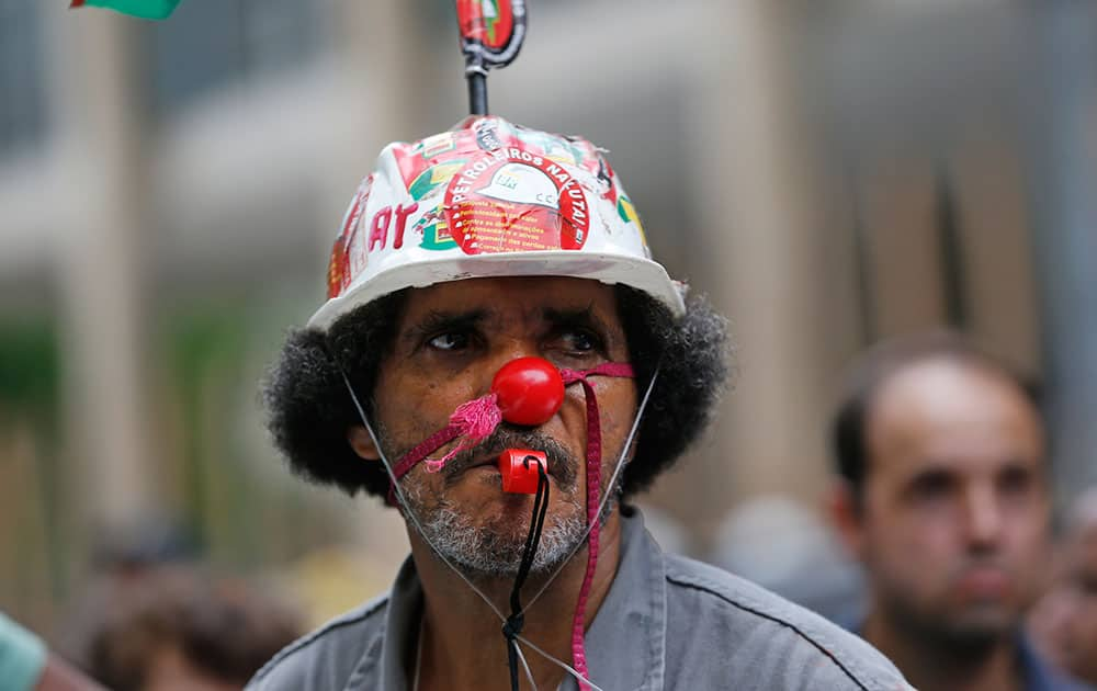 A worker whose company is contracted by Brazil's government-run oil company Petrobras wears a helmet decorated with a sticker that reads in Portuguese