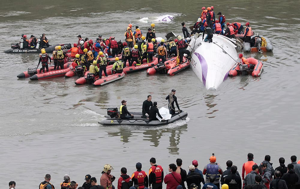 Emergency personnel use a dinghy to bring the body of a passenger in a commercial plane crash to the river shore as others crowd around the plane to rescue other passengers in Taipei, Taiwan.