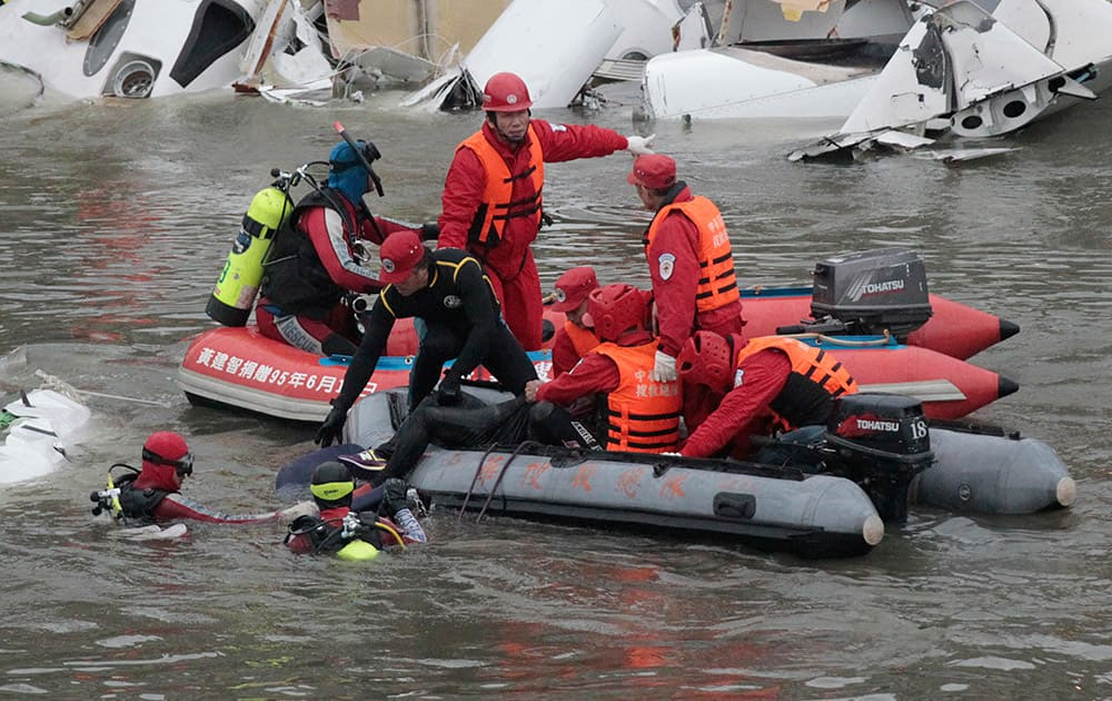Emergency personnel retrieve the body of a passenger of a commercial plane after it crashed in the water in Taipei, Taiwan.