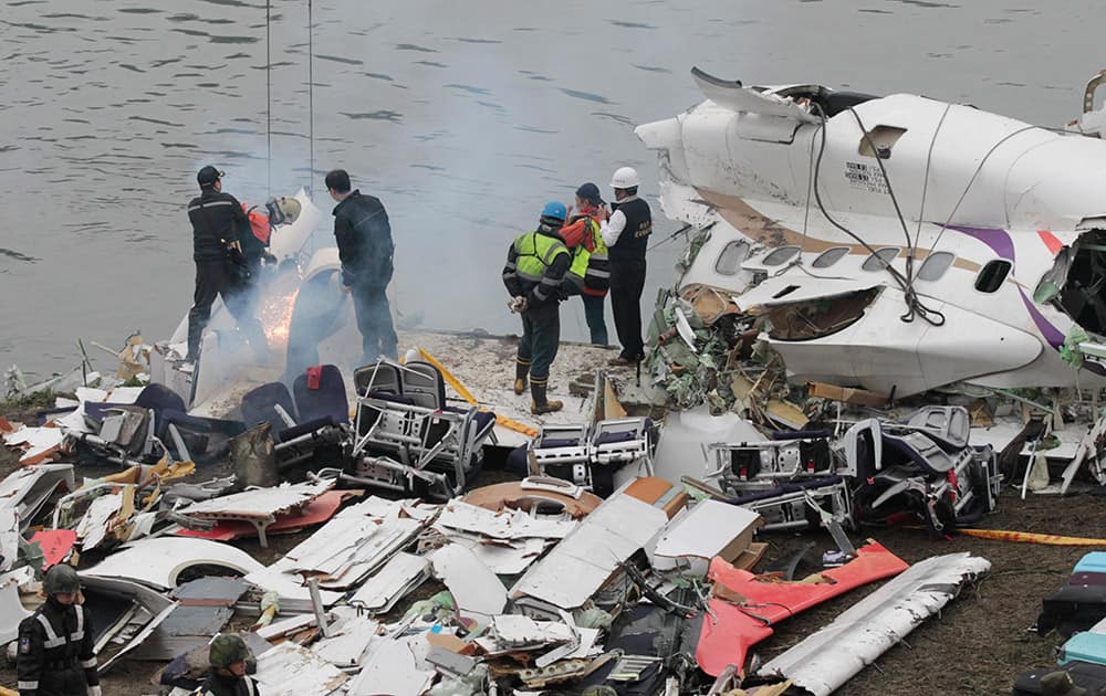Emergency teams break down pieces of wreckage at the site of a commercial plane crash in Taipei, Taiwan.