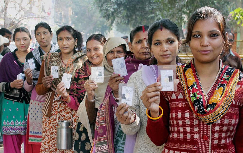 Women voters show their voter ID cards as they wait to cast their votes for the Delhi Assembly elections at Pul Prahladpur, in New Delhi.