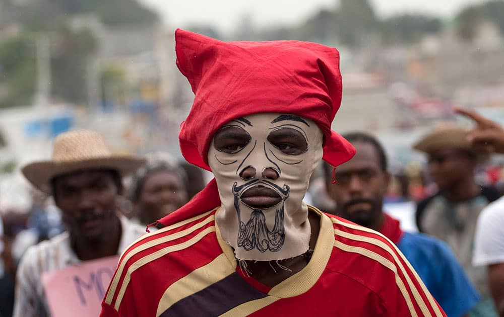 A masked demonstrator attends an anti-government protest in Port-au-Prince, Haiti.