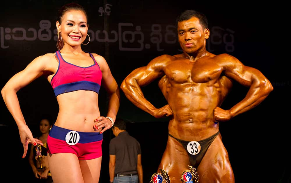 Cherry Maung, left, winner of the model physique and fitness physique contest, poses with Zaw Lin, winner of the bodybuilding contest organized by Myanmar bodybuilder Federation at Myanmar Convention Center (MCC), in Yangon, Myanmar.