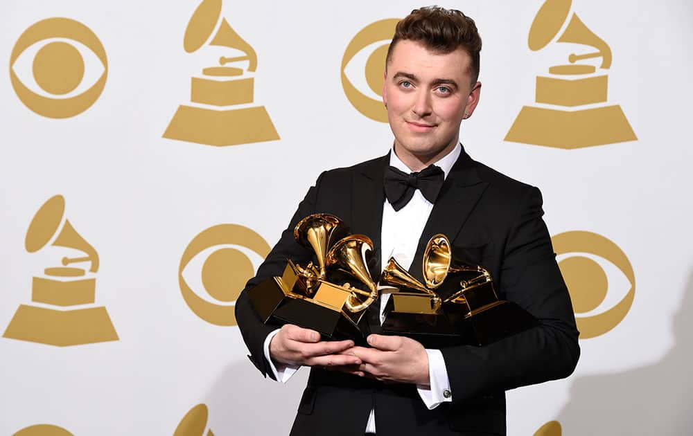 """Sam Smith poses in the press room with the awards for best new artist, best pop vocal album for """"In the Lonely Hour"""", song of the year for """"Stay With Me"""", and record of the year for """"Stay With Me"""" at the 57th annual Grammy Awards."""