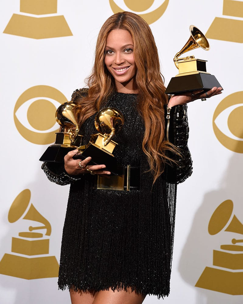 """Beyonce poses in the press room with the awards for best R&B performance for """"Drunk in Love"""", best surround sound album for """"Beyonce"""", and best R&B song for """"Drunk in Love"""" at the 57th annual Grammy Awards."""