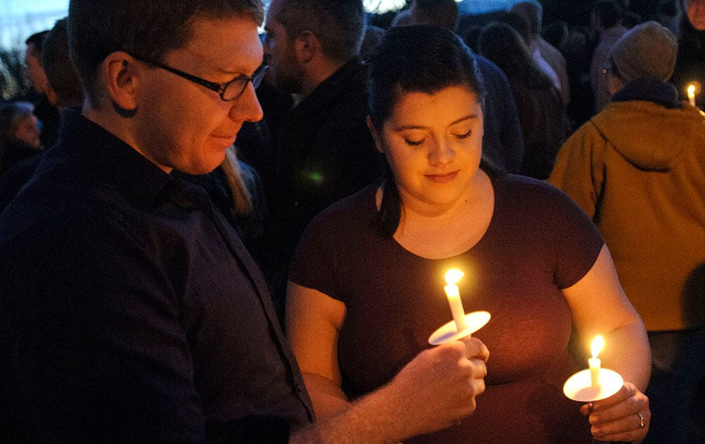 Benjamin Yunker, left, and Brittany Yunker hold candles during a vigil in support of John Dehlin, in North Logan, Utah.