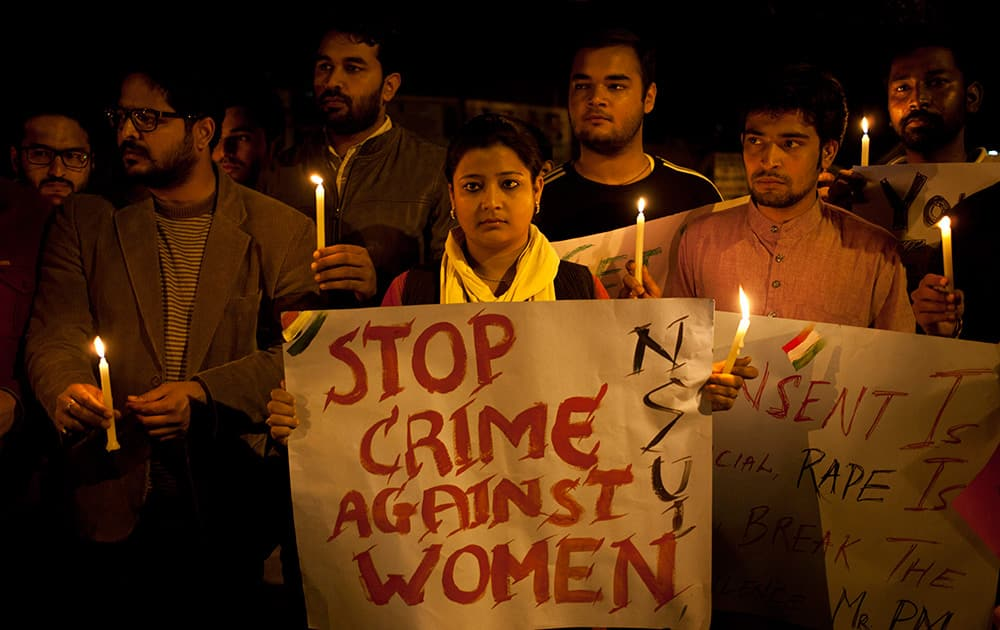 Youth hold candles during a protest against sexual violence in New Delhi. Police were searching Monday for a man who raped a Japanese student sightseeing in northern India, while elsewhere they announced the arrest of eight men suspected of brutally raping and killing a Nepalese woman, as India authorities continue to struggle to address chronic sexual violence.