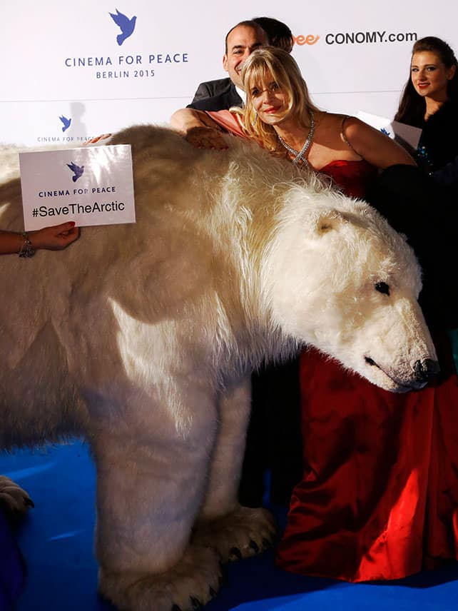 Actress Nastassja Kinski poses with a mock polar bear as she arrives on the red carpet for the Cinema for Peace gala in Berlin.