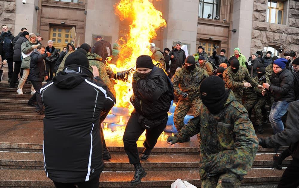 Ukrainian protesters burn tires outside the city council building as they protest against raising the public transport rates in Kiev.