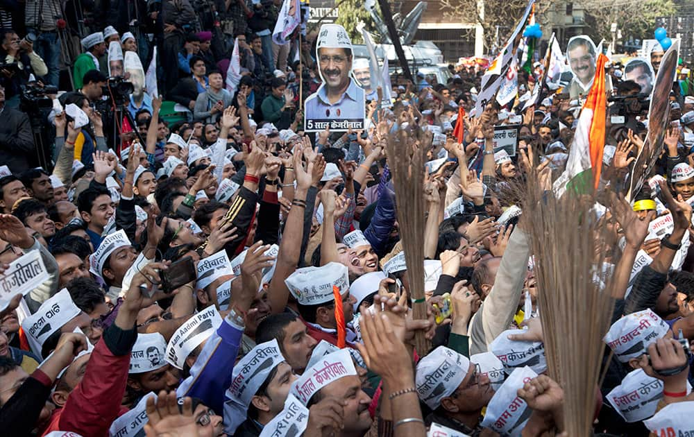 Supporters of the Aam Aadmi Party, holds cut-outs of their leader Arvind Kejriwal and their party symbol, the broom, as they celebrate the party's victory in New Delhi.
