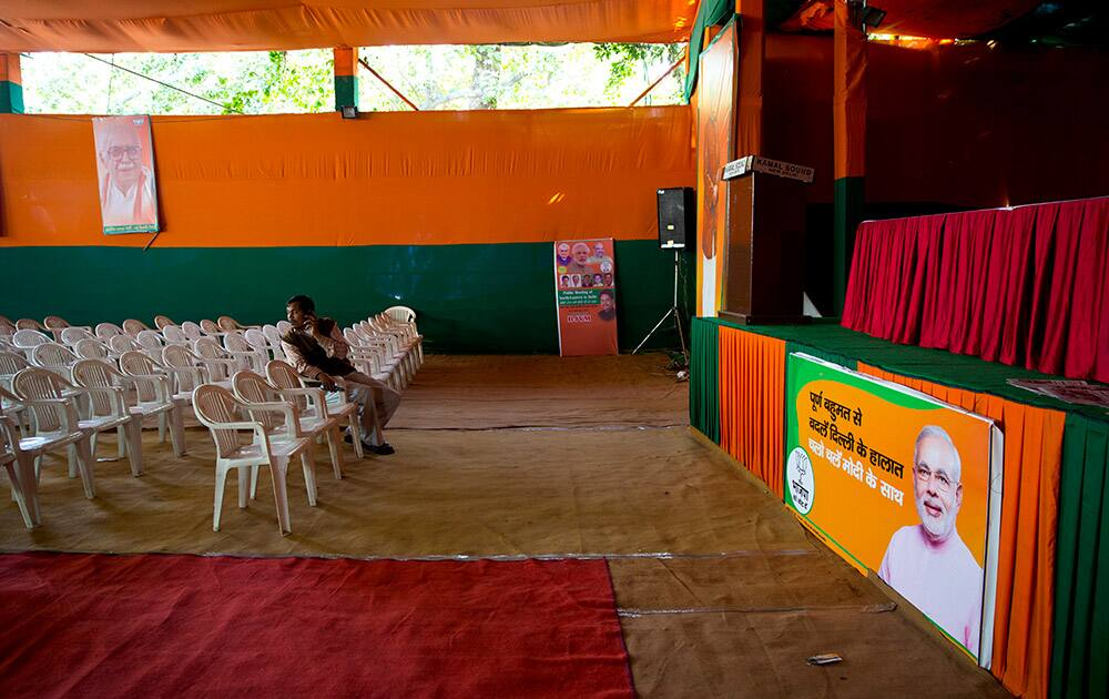 Members of Bharatiya Janata Party (BJP) sits near an empty stage set up for addressing the media at a deserted headquarters of the country's ruling Bharatiya Janata Party (BJP) in New Delhi.