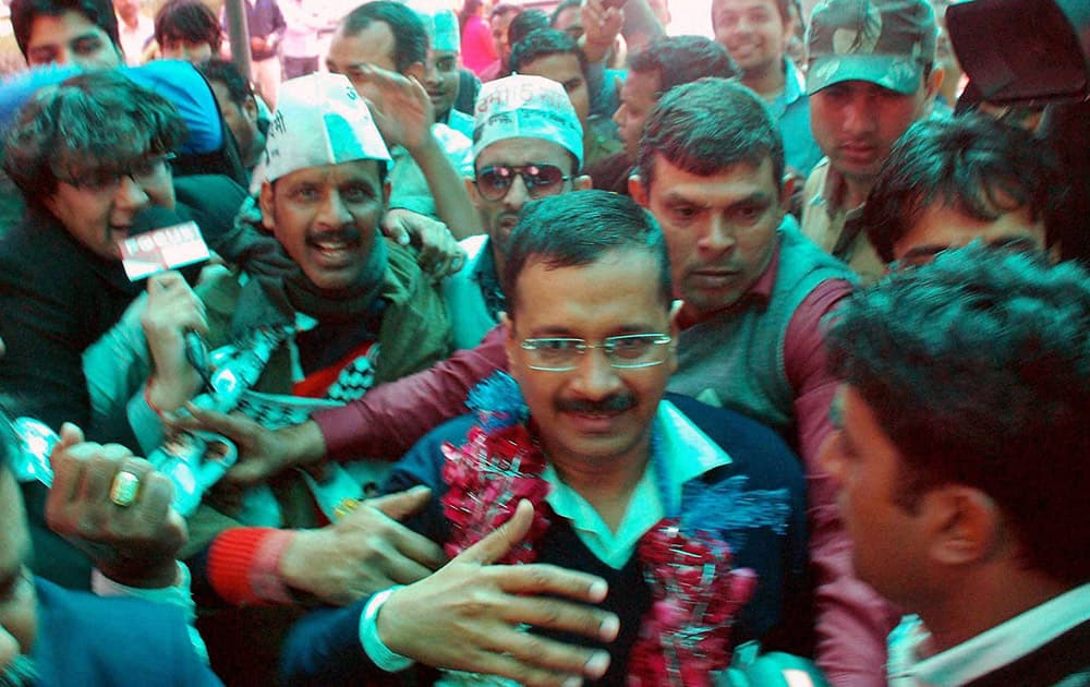 AAP convener Arvind Kejriwal along with suuporters arrives at the party office in Kaushambi on Tuesday after the partys win in Delhi Assembly polls.
