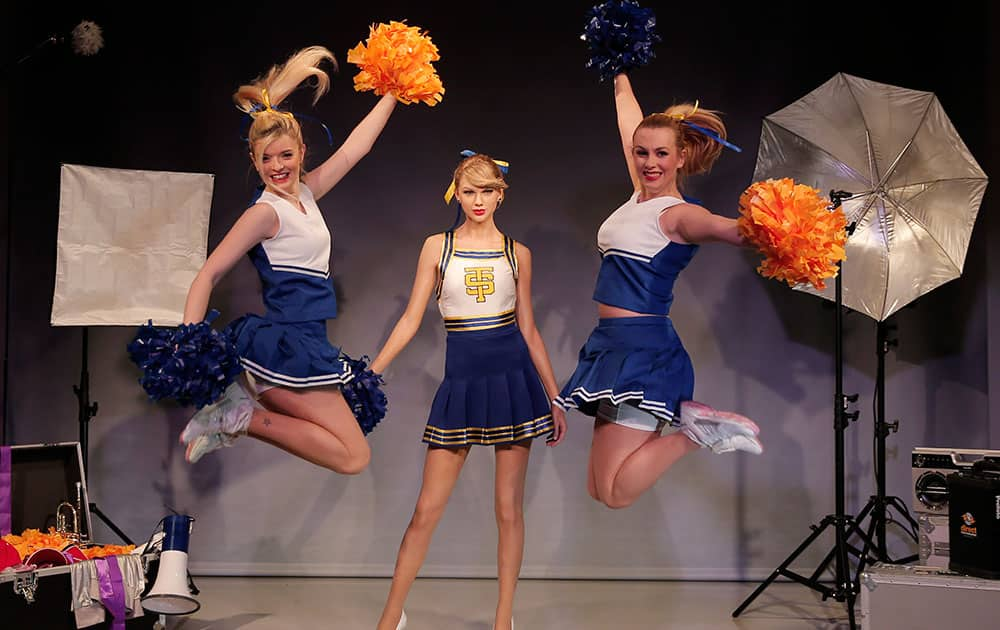 Dancers in cheerleader costumes perform as they pose for the photographers next to a wax figure of US singer Taylor Swift during a photo call in central London.