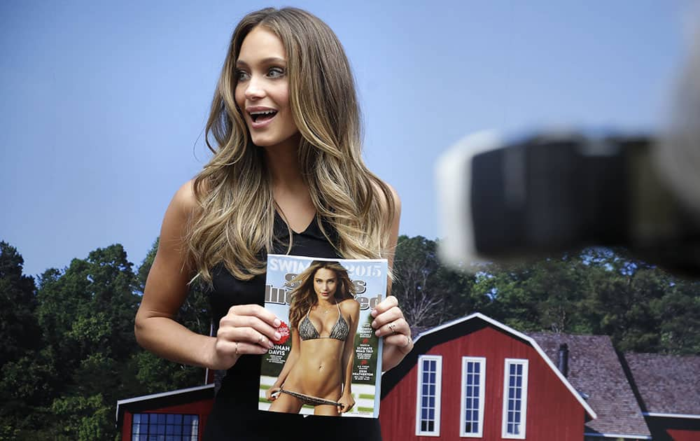 Sport Illustrated swimsuit model Hannah Davis holds her an issue featuring herself on the cover at an event in New York.