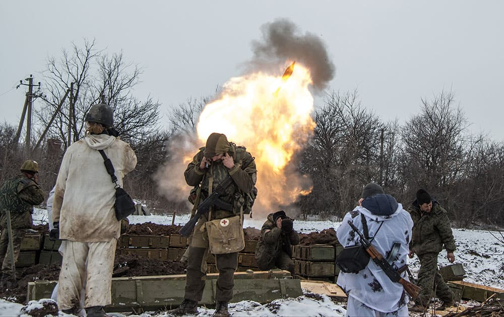Russian-backed separatists cover their ears as they fire a mortar towards Ukrainian troops outside the village of Sanzharivka, northeast of Debaltseve, eastern Ukraine.