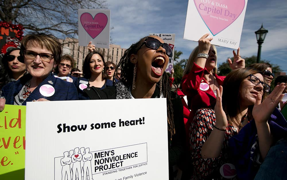 Jamie Allen, a domestic abuse survivor, center, yells in support of a speaker during a rally, at the Capitol in Austin, Texas.