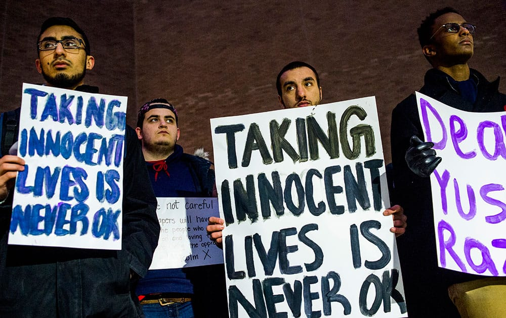 University of Michigan-Flint students, from left to right, Bilal Ali, Michael Puro, Mohamed Samman and Zafir Abutalih attend a vigil at the school in downtown Flint, Mich., in memory of three people who were killed Tuesday near UNC-Chapel Hill, N.C. Craig Stephen Hicks appeared in court Wednesday on charges of first-degree murder in the deaths of Deah Shaddy Barakat, his wife Yusor Mohammad and her sister Razan Mohammad Abu-Salha.