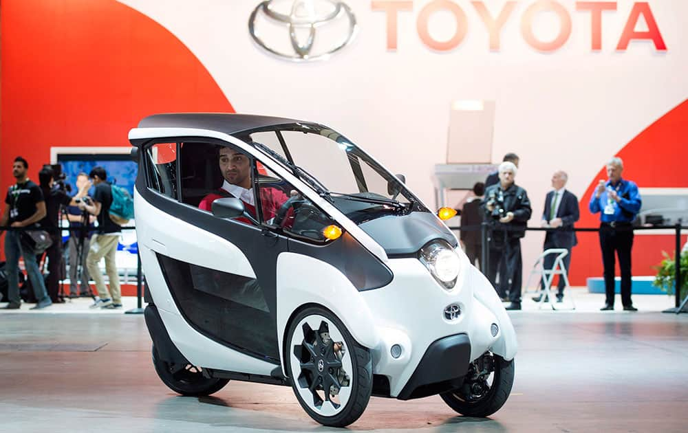 A man tests drives the Toyota i-Road at the 2015 Canadian International Auto Show in Toronto.