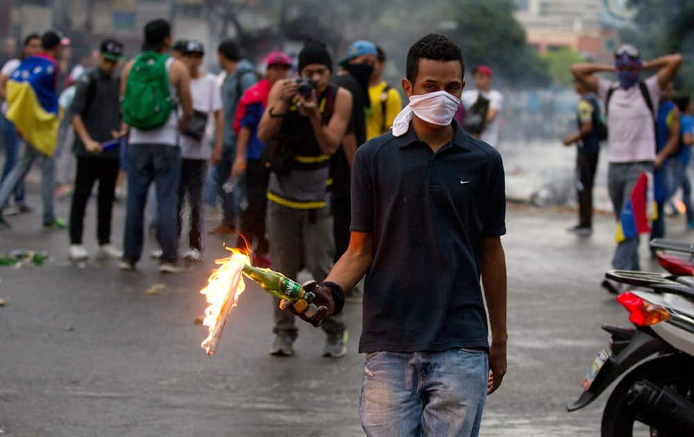 An opposition demonstrator prepares to throw a molotov cocktail at police after clashes broke out at a protest in Caracas, Venezuela.
