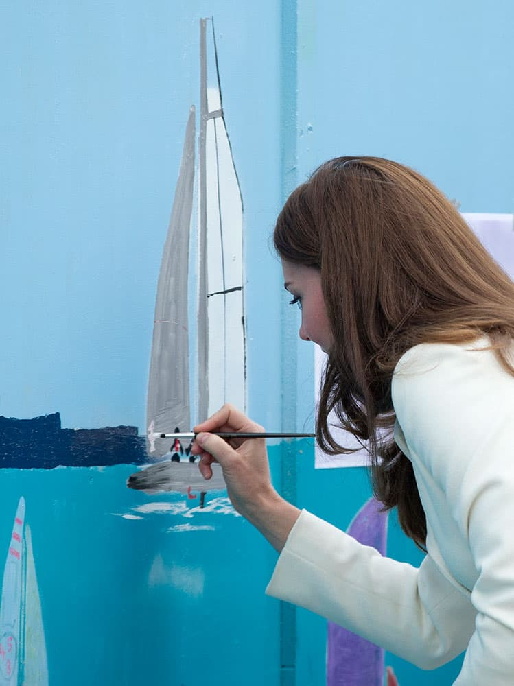 Britain's Kate Duchess of Cambridge applies a dab of paint on a boat as part of a mural outside the new base for Ben Ainslie Racing, in Portsmouth, England.