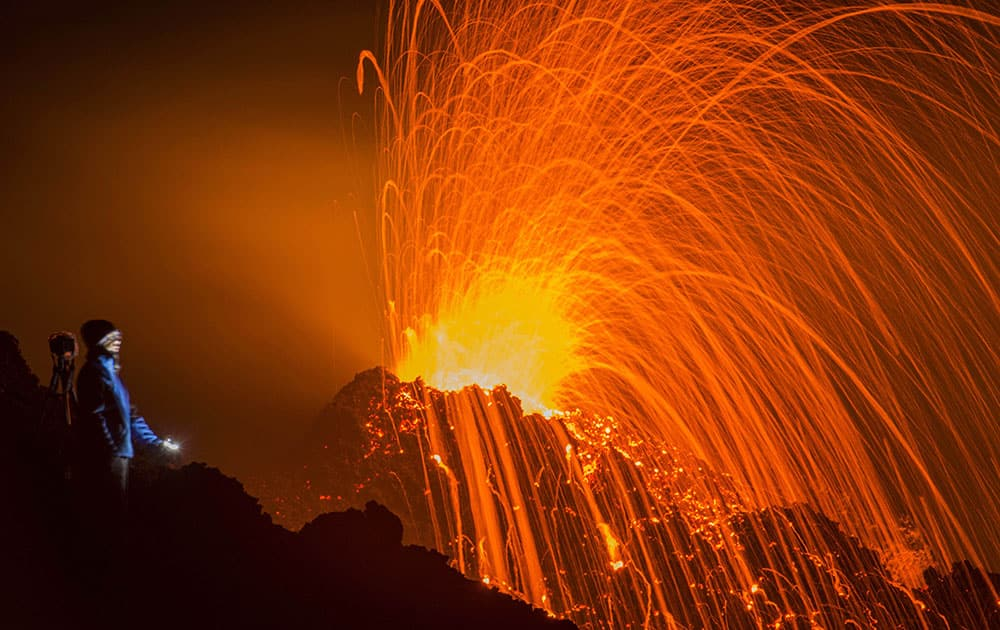 A person looks at the eruptions of the Piton de la Fournaise volcano in the French Indian Ocean island of La Reunion.