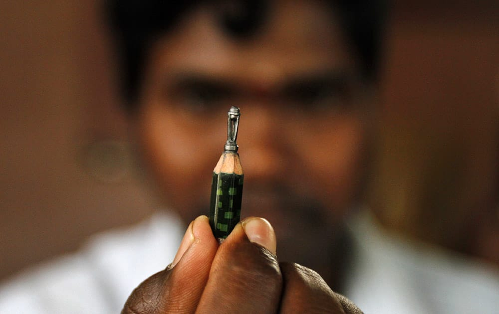 L. Iswar Rao, 32, from Jatni village in Khurda district displays a miniature replica of the ICC World Cup 2015 carved by him on a pencil tip in Bhubaneswar.