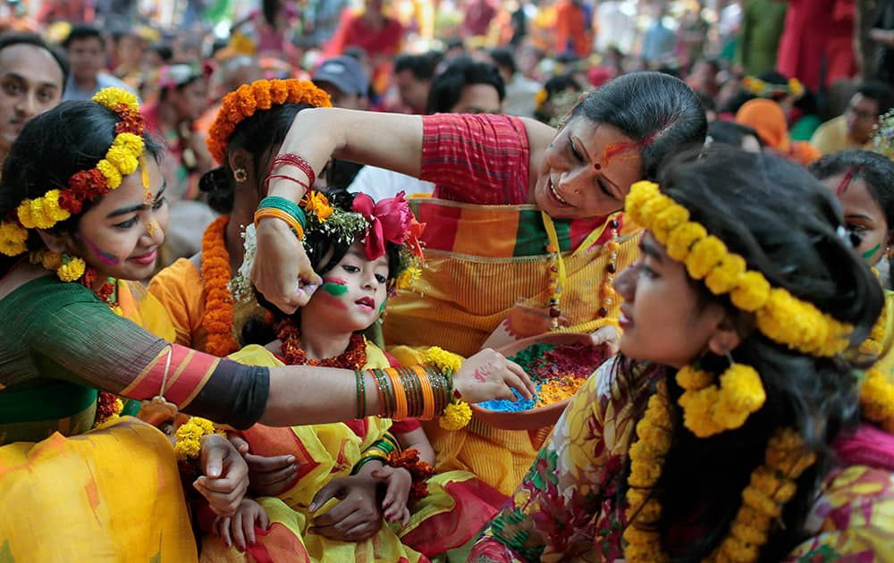 Bangladeshi girls put vermillion powder on each other as they celebrate the arrival of spring on the first day of Falgoon at the Dhaka University campus in Dhaka, Bangladesh.