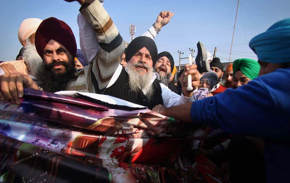 """Sikh protesters hold a poster of Indian religious sect Dera Sacha Sauda chief Baba Ram Rahim Singh's debut film """"MSG: The Messenger of God"""" in Jammu."""