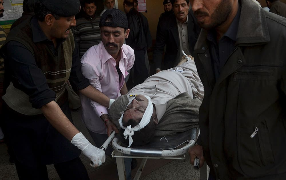 People carry the body of a victim after an attack by suicide bombers and gunmen at a Shiite mosque in Peshawar, Pakistan.