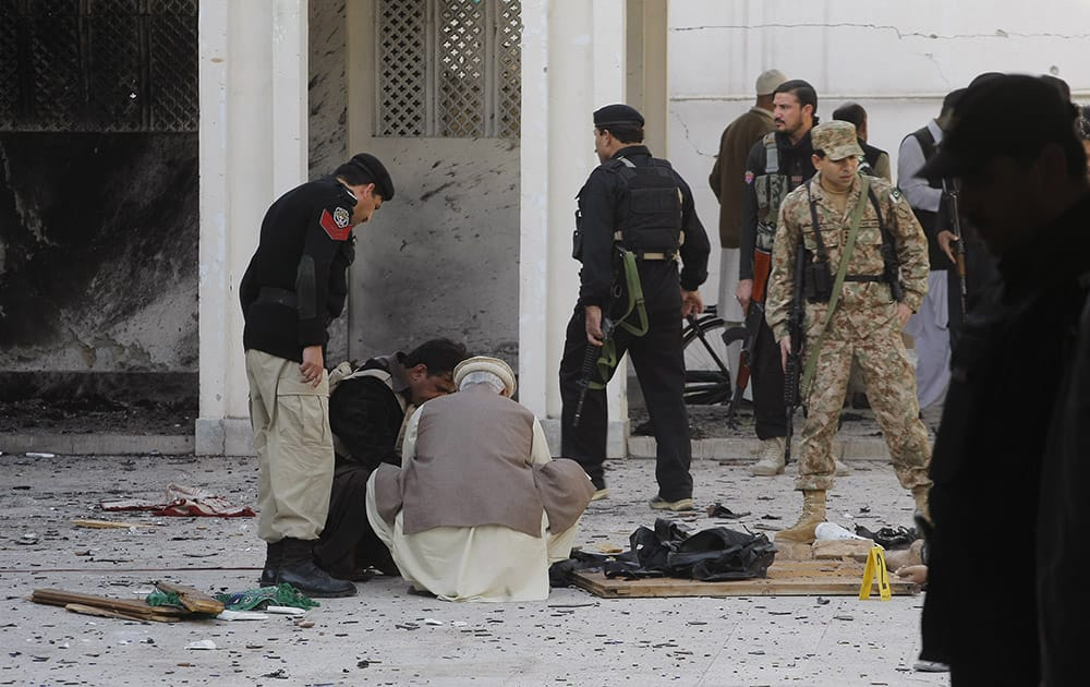 Pakistani security officials collect forensic evidence following an attack by suicide bombers and gunmen at a Shiite mosque in Peshawar, Pakistan.
